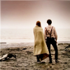 midnightjuly: the eleventh doctor and amy, back on, standing on a beach looking out over the water (time can be rewritten)