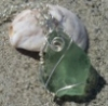 camwyn: A pale greenish piece of triangular sea glass wrapped in a little silver wire to make a pendant (jewelry)