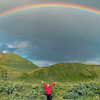 wendelah1: a person in a meadow looking up at a rainbow (A Blessing)