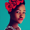 bilqis: lupita nyongo looking at the camera, a red rose flower crown on her head (stock: oya colors)