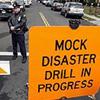 "john: Orange warning sign on street. Sign reads ""MOCK DISASTER DRILL IN PROGRESS"" (mock: disaster drill in progress)"