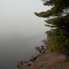 writerproblem193: A foggy grey lake, with the horizon line invisible. On the left is an island with a pine. (algonquin)