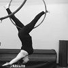 niqaeli: person suspended upside down from a metal hoop by their feet, which are spread as though mid-stride (lyra)
