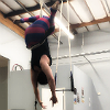 niqaeli: person suspended upside from a trapeze which is wrapped around them in a harness-like wrap, legs crossed around the ropes (trapeze)