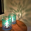 rosefox: Two small glass candleholders with a green and blue tree design cast a tree-shaped shadow. (Judaism-peace)