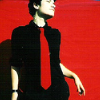 pospreterito: young man in black with a red tie against a red wall (Default)