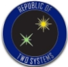 "republicoftwosystems: an enamel pin in the shape of a blue circle with two stars, one yellow one green, and the words ""Republic of Two Systems"" around the outside of the circle. (Ro2S)"