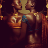 sylvaine: A photo of two black women wearing colourful, revealing clothes and beautiful jewellery, one from the front and one from the back. They are half-embracing and looking into each other's eyes with great dignity. ([gen:sj] beauty and power)