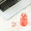 sesquidrabbles: Glass jar filled with some red liquid lying next to a white laptop, a few red paper clips lying by its side (Sesquidrabbles Icon)