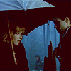 eulalia: Scully and Mulder standing under an umbrella in the woods (rainy days)