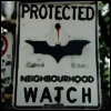 harpers_child: a neighborhood watch sign where the typical icon has been replaced with a batman signal (DC: the bat is watching)