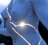 """iodama: A woman's torso, stone, cracked, with light blazing forth from within her chest; a close up photo of Paige Bradley's sculpture, """"Expansion"""", actually bronze not stone. (Default)"""
