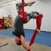 truelove: An adult human female is upside down, hanging from a harness of aerial silks.  One leg is crossed over the silks over her head and the other is wrapped in a silk and being pulled down behind her back and head in a scorpion position. (aerial, circus, silks)