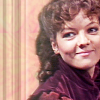 auroracloud: Nyssa of Traken from Classic Doctor who, a young white woman with curly brown hair and burgundy red velvet outfit, smiling (Nyssa smile)