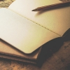 auroracloud: a stack of notebooks, one of them open and with pencil lying on top of it (writing notebooks)