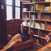 auroracloud: a woman wearing a short dress and sitting on a sofa, reading with her face hidden behind the book, next to bookshelf (reading: on the sofa)
