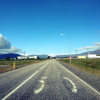 nerakrose: photo of a straight road with the number 50 painted on the right lane. in the background are low houses and a low mountain with a glacier. the sky is blue. (road)