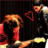 sylvaine: Gerard looking at Ray, who's concentrating on his guitar. There's a red <3 between them. ([band:MCR] Gerard&Ray <3)