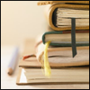 athousanderrors: a pile of books, bookmark ribbons hanging out, and a pen at the side. (books)