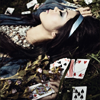 unavoidedcrisis: girl lying on the ground with playing cards scattered over her (little singing bird)