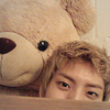 hokuton_punch: Photograph of Jang Dongwoo from Infinite hiding behind a table with a giant teddy bear. (dongwoo infinite cuteface)