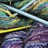 dmarley: Hanks of purple and green yarn with knitting needles on top (Knitting)