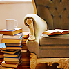 delphi: A photograph of an armchair with a tall stack of hardcover books and a coffee cup next to it.. (rainy day recs)