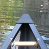 antimony: photo of the bow of a canoe in the water taken from inside the canoe. (canoeing)