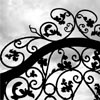 ivoryandhorn: An ornate wrought iron gate silhouetted against a cloudy sky. (gen: spare vocabulary)
