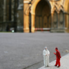 skygiants: a figure in white and a figure in red stand in a courtyard in front of a looming cathedral (cour des miracles)