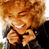 miarrow: photo of antonia thomas grinning widely and holding her jacket (Antonia Thomas : FACE ATTACK)