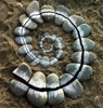 ambyr: pebbles arranged in a spiral on sand (nature sculpture by Andy Goldsworthy) (Pebbles)