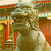 qilin: A brass qilin statue in front of a red Chinese building. (brass)