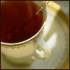 serpentine: a cup of tea on a saucer with a spoon in it (Food - Tea)
