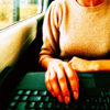 watersword: A woman typing on a laptop next to a window (on a train, perhaps?) (Stock: laptop on a train)