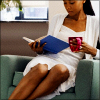 newtypeshadow: Black woman wearing white sits in a green cushy chair while reading a blue book and holding a red mug. (Default)