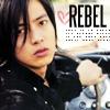 """jain: Yamapi at the wheel of a car. Text: """"Rebel"""" (yamapi)"""
