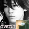 "jain: Kame, closeups of his face and turtle earring. Text: ""Turtle"" (kame)"