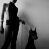 alison_alice: A girl holding the leash of a sitting doberman (doberman girl)