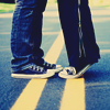 nervesinpatterns: boy and girl from the knees down, toe to toe, standing on double yellow lines in the road (Your life story?...please.)