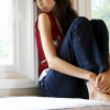 elizabeth: woman sitting next to a window in jeans and bare feet (quiet, window)