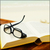twtd: thick rimmed glasses on an open book (Stock- book with glasses)