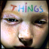 "iconoplast: A young girl with freckles.  The word ""things"" is written in multicolored letters on her forehead. (things)"