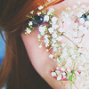 rainfall: A girl holds flowers in front of her face and peers through them. (little white flowers)