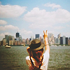 rainfall: A girl in a hat reaches for the skyline of a distant city. (reach for the sky)