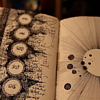 thiefofvoices: A book open to a page with arcan hand-drawn symbols on it. (arcane)