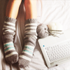 afuna: Hand-knit pair of socks on feet, beside a ball of yarn with knitting needles and the keyboard of a laptop (knitting)