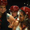 theleaveswant: A team of roller derby skaters in red helmets; one (Iron Maven) makes pistol hands and smiles over her shoulder (see what I did there?)