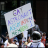 "quadruplify: Gay pride parade participant, dressed as astronaut, holding sign that reads: ""Gay Astronaut Association Members: 1"" ([Other] LGBTQ+ - gay astronaut)"