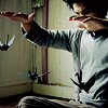 smallwolf: a man with origami cranes on strings hanging from his fingers (i only *think* i know what i'm doing)